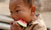 A kid with a funny expression on his face eating a watermelon.