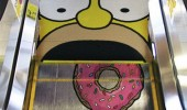 An escalator that is painted with Homer Simpson eating donuts.